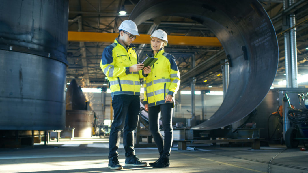 Male and Female Industrial Engineers in Hard Hats Discuss New Project while Using Tablet Computer. They Make Showing Gestures.They Work at the Heavy Industry Manufacturing Factory.
