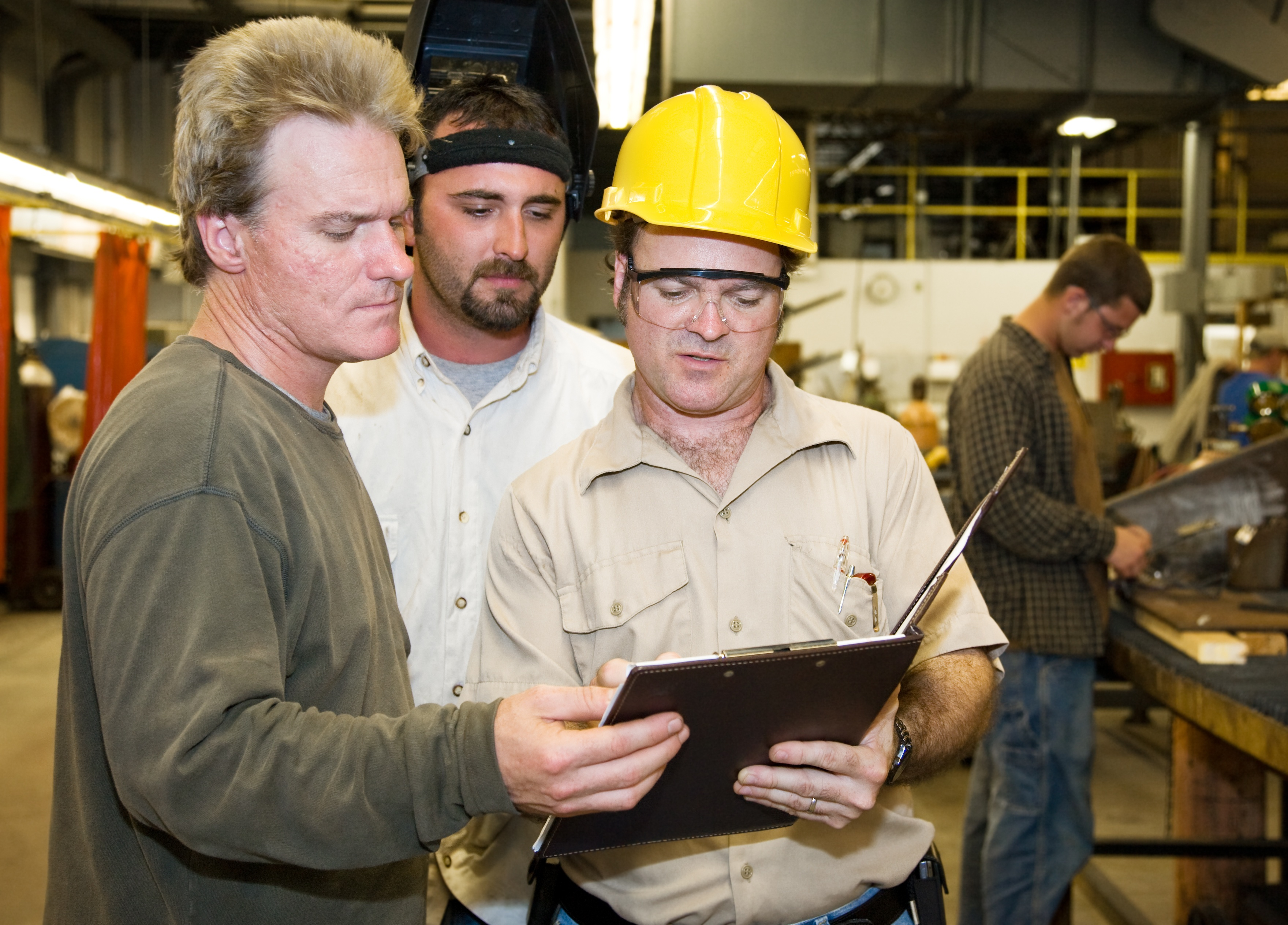 Factory worker and foreman discuss inspection report with OSHA auditor.