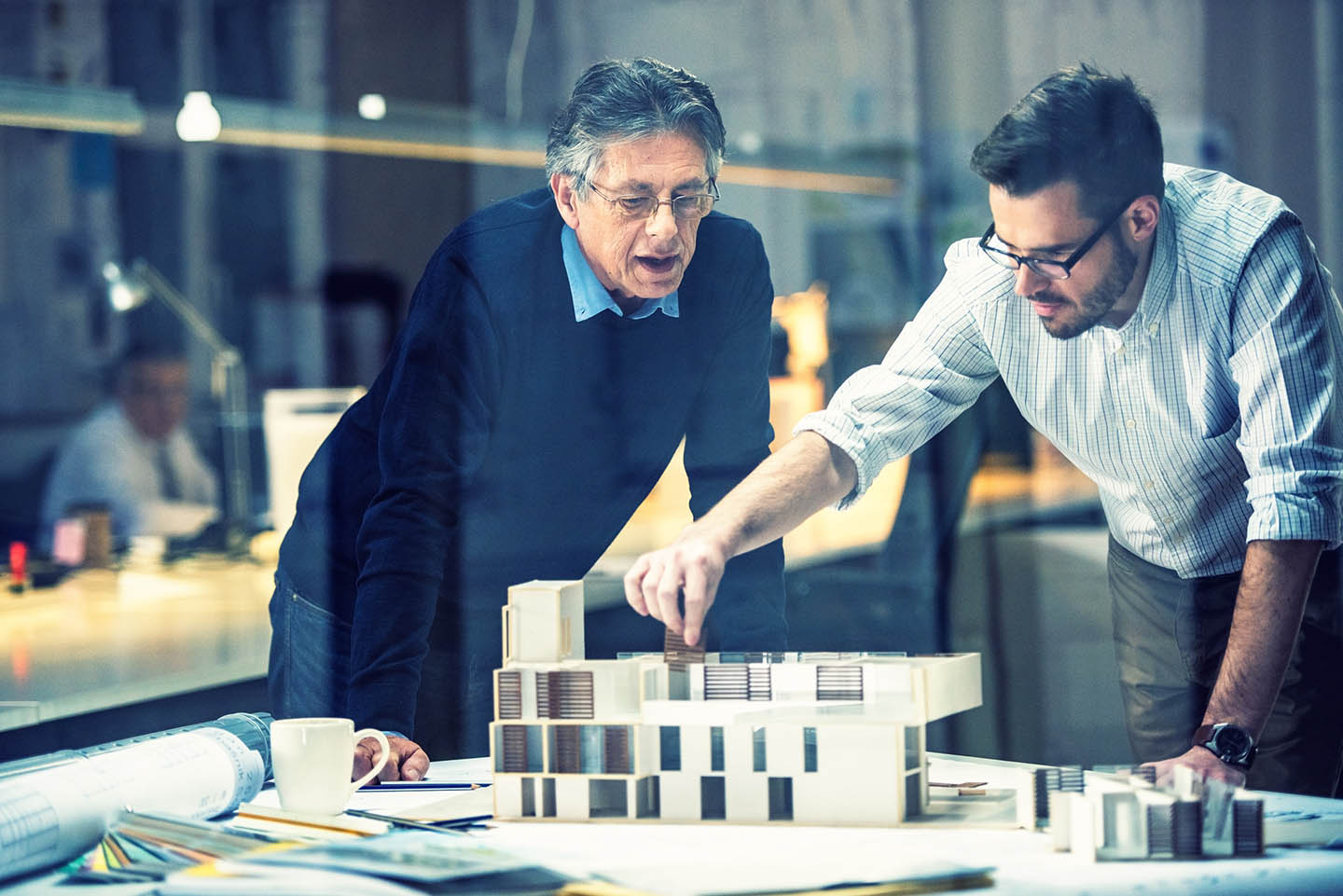 Young architect explaining project plan to senior coworker in the office with the help of an architectural model, shot through glass.