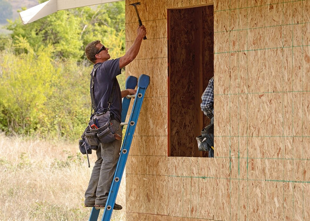 Young man on ladder hammering house