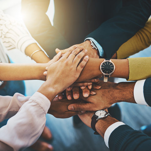Closeup shot of an unrecognizable group of businesspeople joining their hands together in a huddle